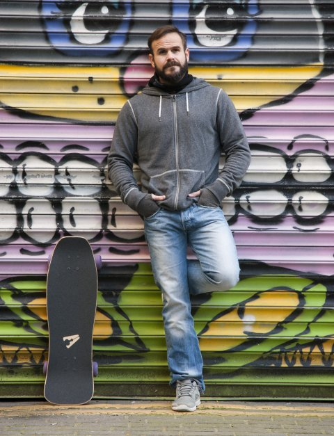 Male skateboarder leaning against shutter with street art by Sweet Toof, Rowdy and Shuby